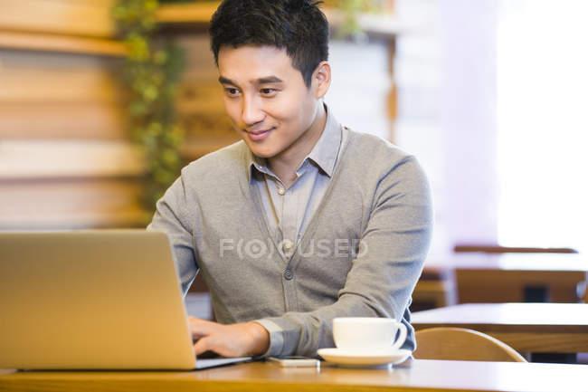 Uomo cinese che utilizza il computer portatile in caffetteria — Foto stock