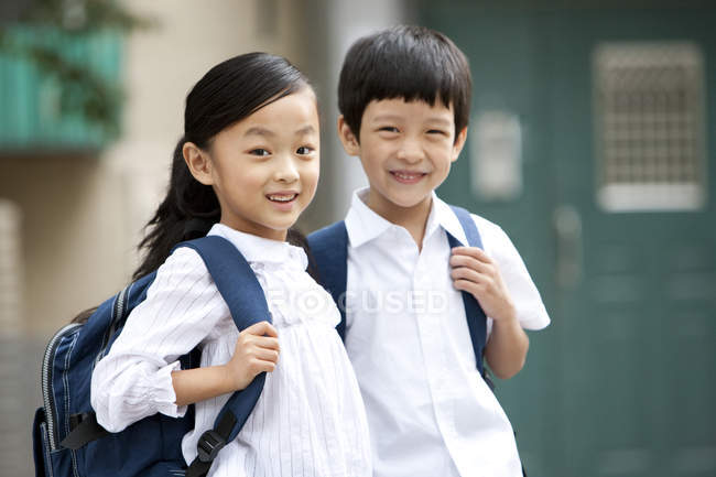 Chinese children with backpacks posing on street — Stock Photo