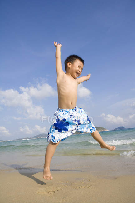 Happy kid jumping with arms outstretched at beach — Stock Photo
