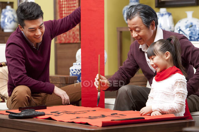 Girl with father and grandfather doing Chinese calligraphy — Stock Photo