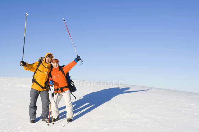 Chinese couple posing with ski poles in air — Stock Photo