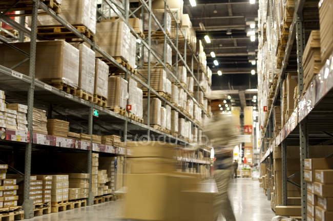 Movimento desfocado tiro das caixas empurrando de trabalhador de armazém — Fotografia de Stock