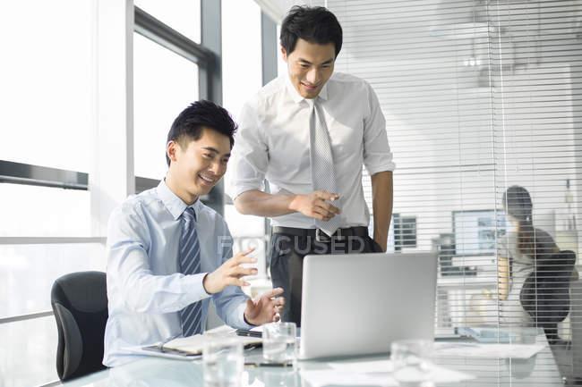 Китайские бизнесмены обсуждают работу в офисе — стоковое фото