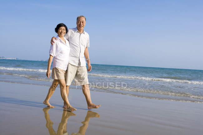 Старшая китайская пара прогуливаясь вдоль морского пляжа — стоковое фото