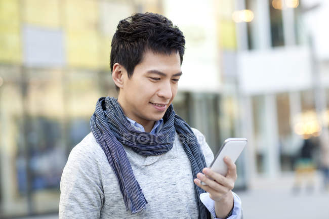 Fashionable Chinese man using smartphone on city street — Stock Photo