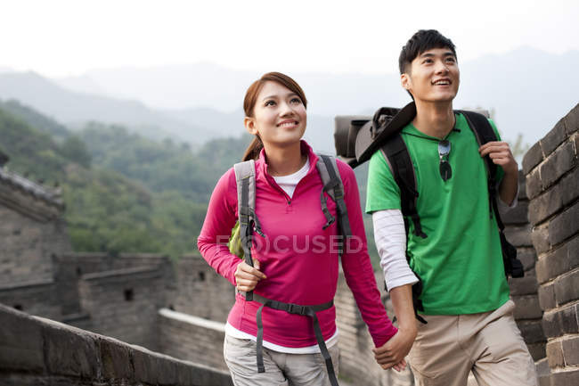 Chinese couple holding hands and looking at view on Great Wall — Stock Photo