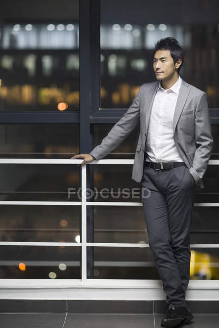 Chinese businessman leaning on railing at office building and looking away — Stock Photo