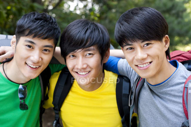 Chinese male backpackers embracing and looking in camera — Stock Photo