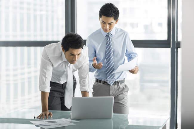 Les hommes d'affaires chinois utilisant un ordinateur portable et parlant au bureau — Photo de stock