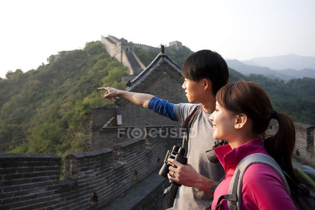 Chinese couple with binoculars pointing at view on Great Wall — Stock Photo