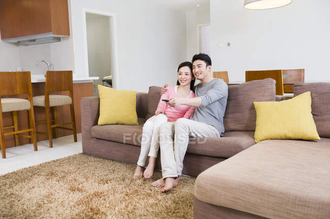 Chinese couple watching TV on sofa in living room — Stock Photo