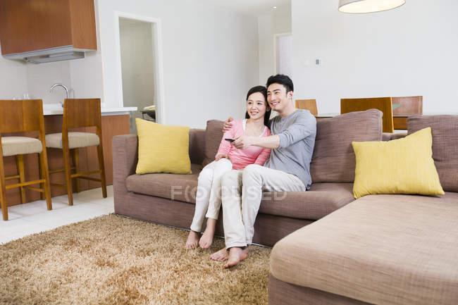 Chino par ver Tv en el sofá en salón - foto de stock