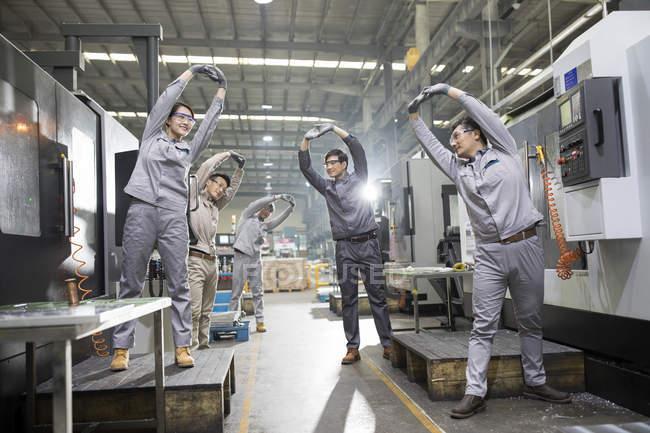 Chinesische Ingenieure stretching am Industriebetrieb — Stockfoto