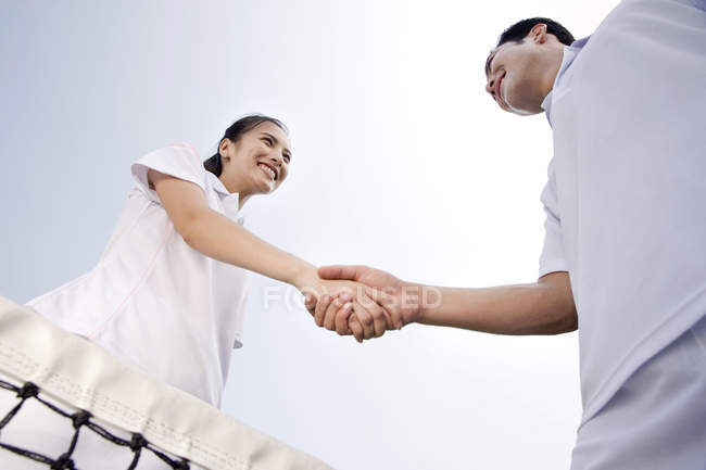 Chinese couple shaking hands on tennis court, low angle view — Stock Photo