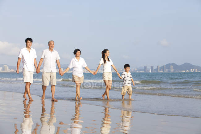 Chinese family holding hands and walking on beach — Stock Photo