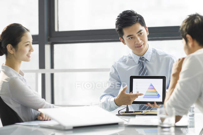 Chinese businessman presenting graph on digital tablet screen in office — Stock Photo