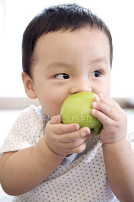 Китайский младенец ест зеленое яблоко и смотрит в сторону — стоковое фото