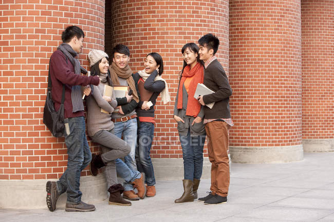 Chinese college students chatting in front of university building — Stock Photo