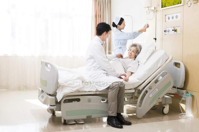 Médico chinês usando o estetoscópio do paciente no hospital — Fotografia de Stock