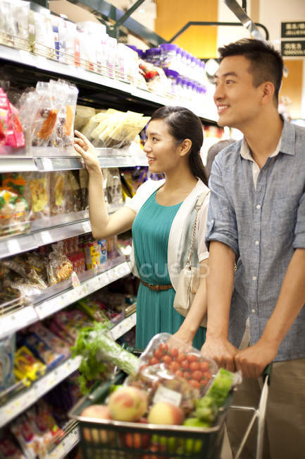 Chinese Couple Shopping In Supermarket With Cart Selective