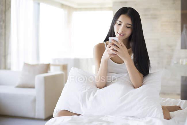 Donna cinese utilizzando smartphone sul letto al mattino — Foto stock