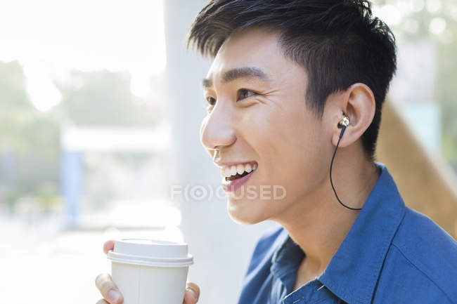 Chinese man drinking coffee and listening music in earphones — Stock Photo