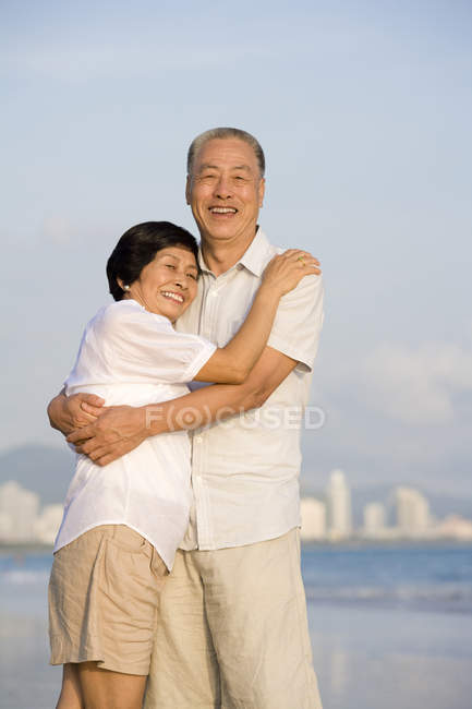 Senior Chinese couple embracing on beach — Stock Photo