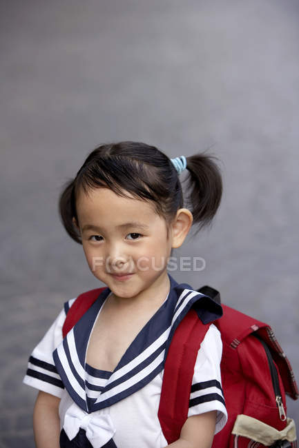 Chinese girl in school uniform with backpack — Stock Photo