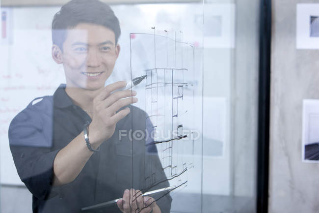 Chinese male designer drawing sketch on glass wall — Stock Photo