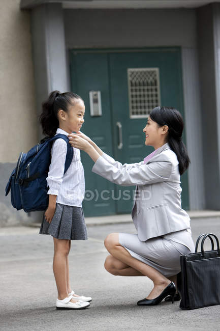 Chinese mother adjusting daughter school uniform on street — Stock Photo