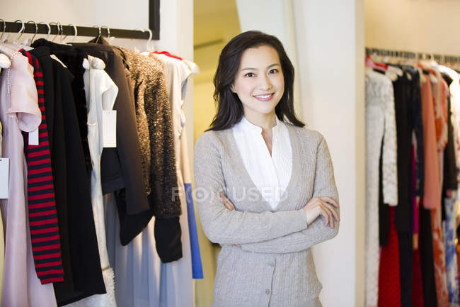 Chinese woman standing with arms crossed in clothing store — Stock Photo