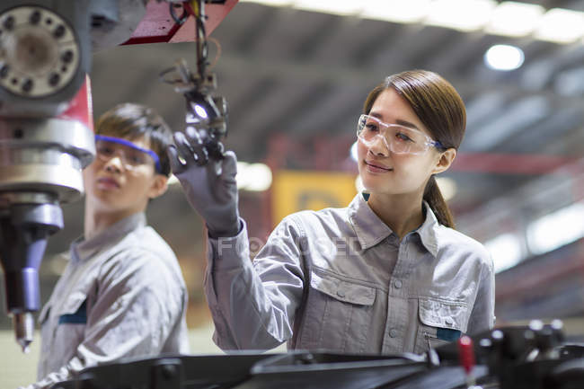 Chinese male and female engineers working with machine in factory — Stock Photo