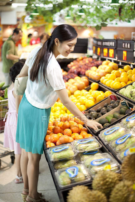 Chinese woman choosing fruits in supermarket — Stock Photo