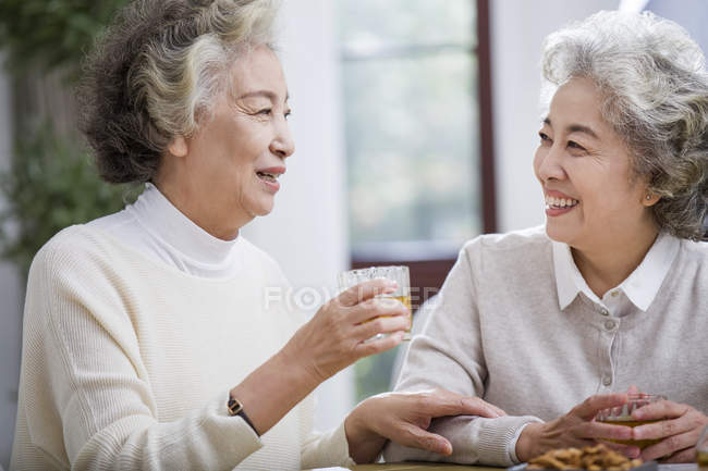 Senior Chinese women talking and drinking tea — Stock Photo