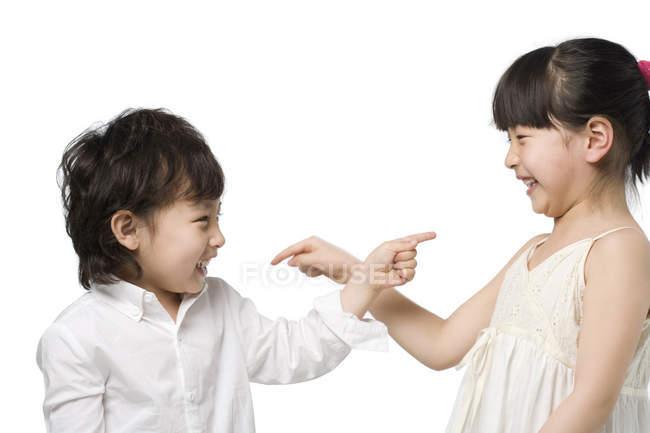 Niños asiáticos apuntándose unos a otros sobre fondo blanco - foto de stock