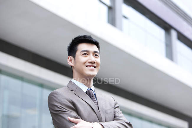 Smiling Chinese businessman with arms crossed in front of business building — Stock Photo