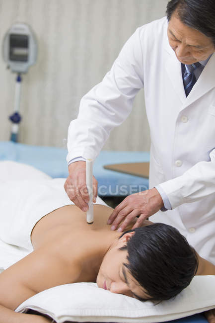Старший китайський лікар даючи moxibustion терапії, щоб пацієнт — стокове фото
