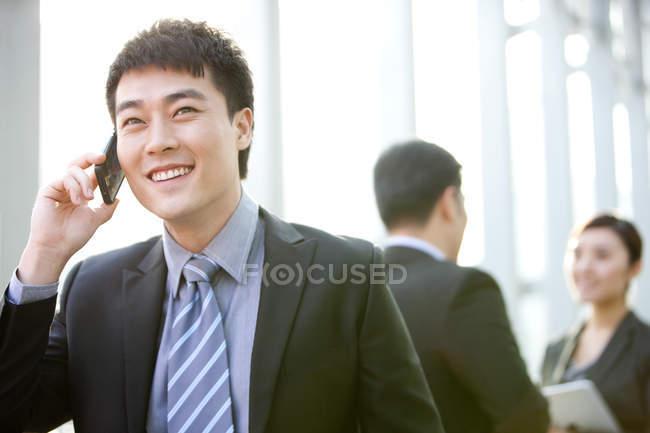 Китайский бизнесмен разговаривает по телефону с коллегами в фоновом режиме в помещении — стоковое фото