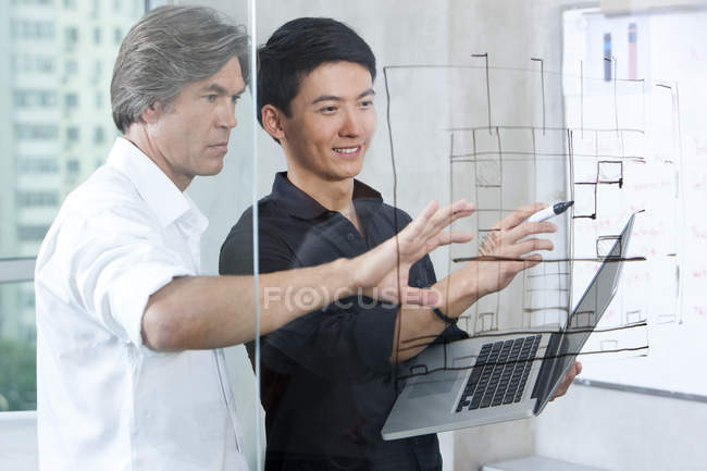 Designers drawing sketch on glass wall — Stock Photo