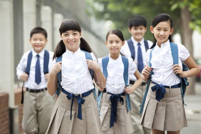 Chinese schoolchildren in school uniform posing in street — Stock Photo