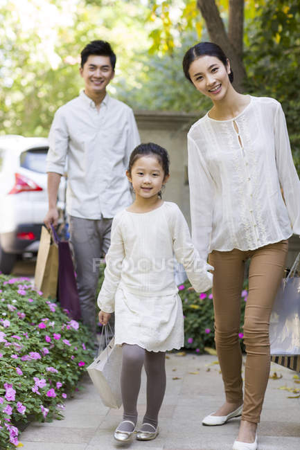 Chinese parents and daughter coming back from shopping — Stock Photo
