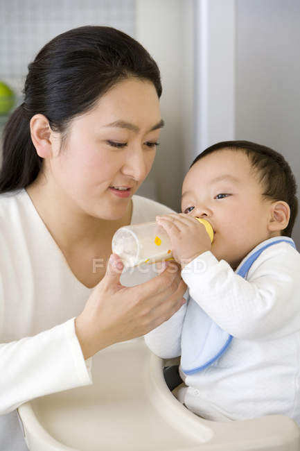 Chinese woman feeding baby son with bottle in high chair in kitchen u2014 Stock Photo  sc 1 st  Focused Collection & Chinese woman feeding baby son with bottle in high chair in kitchen ...