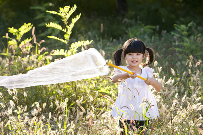 Little Chinese girl playing in meadow with butterfly net — Stock Photo