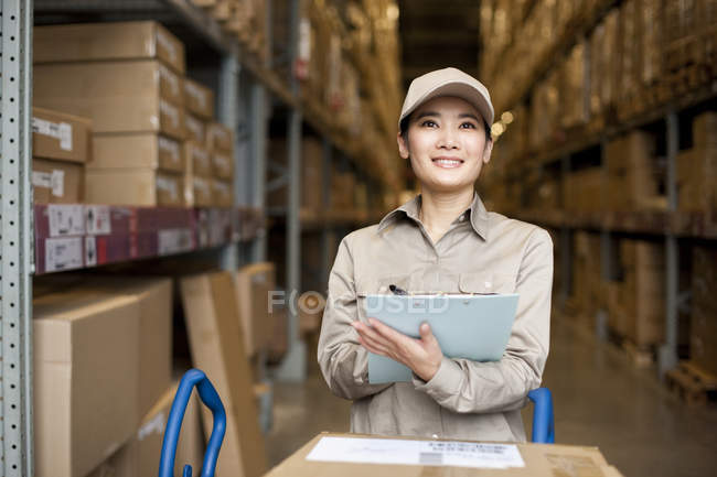 Female Chinese warehouse worker doing inventory — Stock Photo