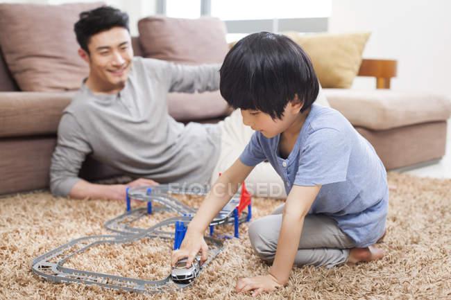 Cinese padre e figlio che giocano macchinina in salotto — Foto stock