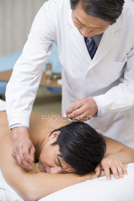 Senior chinese doctor giving acupuncture to male patient — Stock Photo