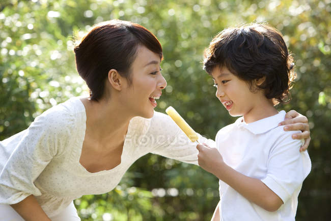 Chinese boy sharing ice pop with mother outdoors — Stock Photo