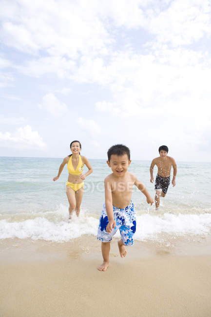 Parents chasing son at sea beach — Stock Photo