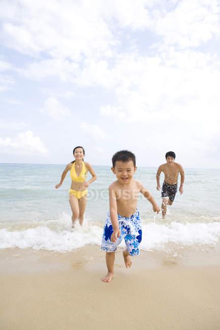 Родители, чеканка сына на море пляж — стоковое фото