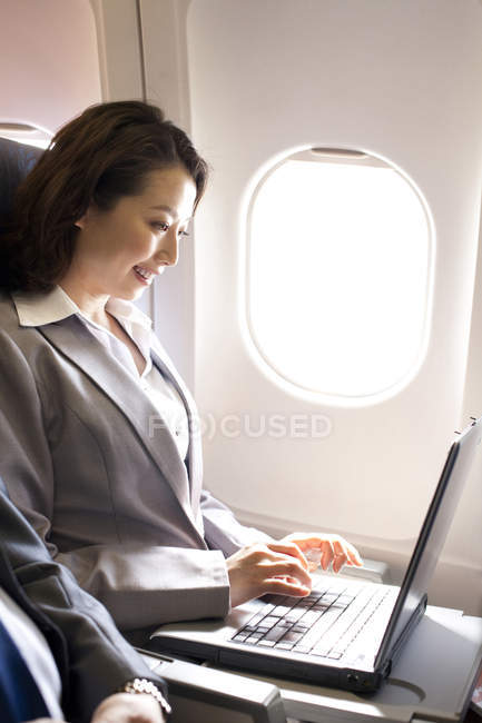 Empresária chinesa usando laptop no avião — Fotografia de Stock
